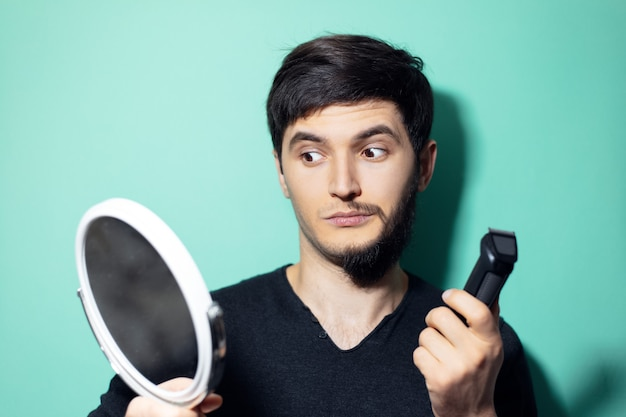 Young surprised man with half shaved face, looking in mirror  on wall of aqua menthe color.