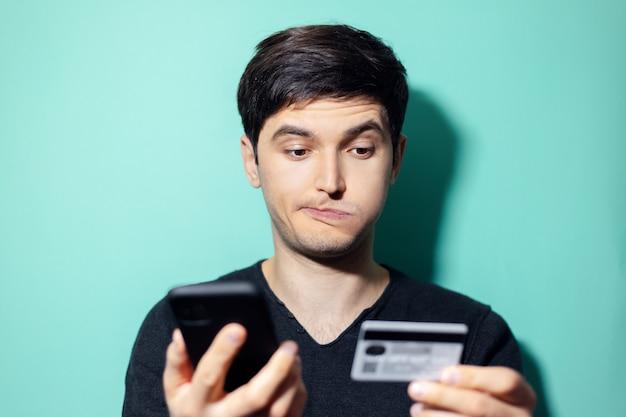 アクアメンテ色の壁にスマートフォンとクレジットカードを手に若い驚きの男。