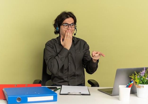 광학 안경에 헤드폰에 젊은 놀란 회사원 남자 사무실 도구를보고 복사 공간이 녹색 배경에 고립 된 노트북을 가리키는 책상에 앉아