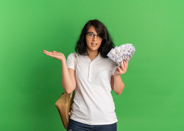 Young surprised pretty caucasian schoolgirl wearing glasses and back bag holds money and keeps hand straight on green  with copy space