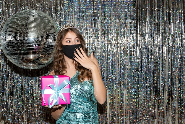 Giovane donna graziosa sorpresa che indossa un abito lucido con paillettes con corona nella mascherina medica nera e che tiene un regalo nel partito