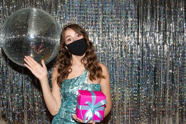 Giovane donna graziosa sorpresa che indossa un abito lucido con paillettes con corona nella mascherina medica nera e che tiene un regalo che indica qualcosa nel partito