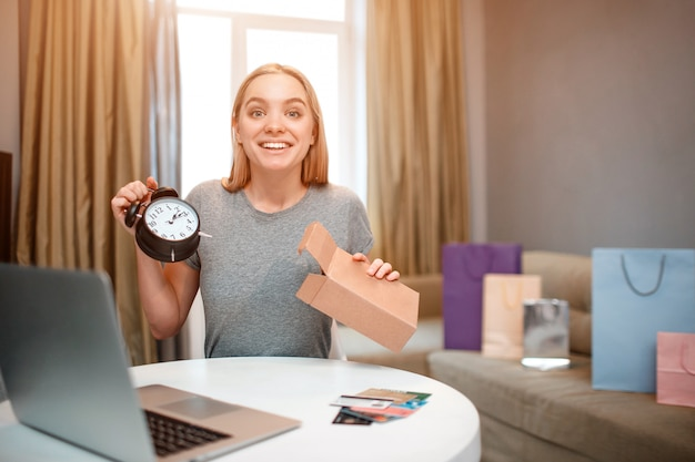 Young surprised shopper is unboxing parcel with fashion clock