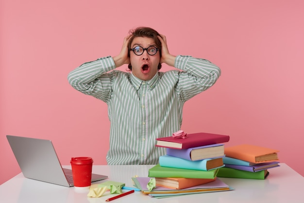 Young surprised student in glasses, sits by the table and working with laptop, covers his ears and shouts , isolated over pink background.