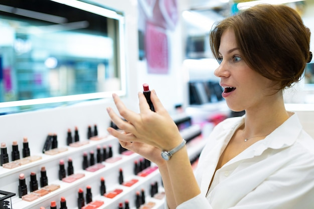 Young surprised woman in decorative cosmetics shop is choosing lipstick