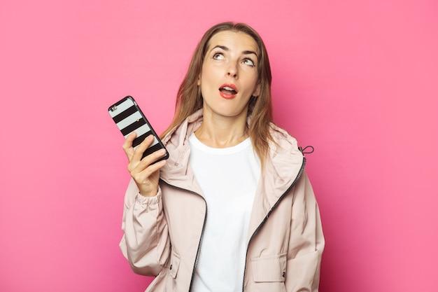 Молодая удивленная женщина, держащая телефон, изолированный пинк.
