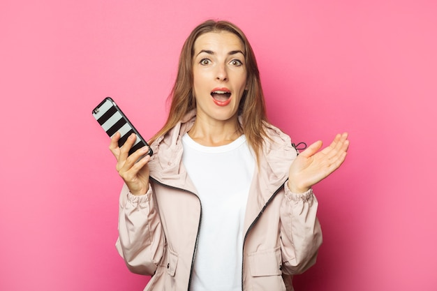 Young surprised woman holding a phone, pink isolated.