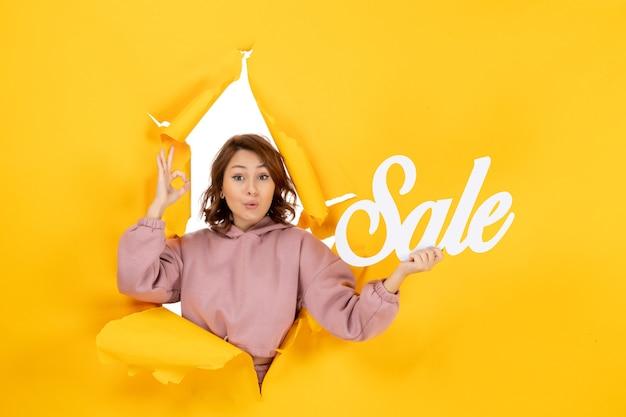 黄色の引き裂かれた画期的な背景に販売サインを保持している眼鏡ジェスチャーを作る若い驚きの女性