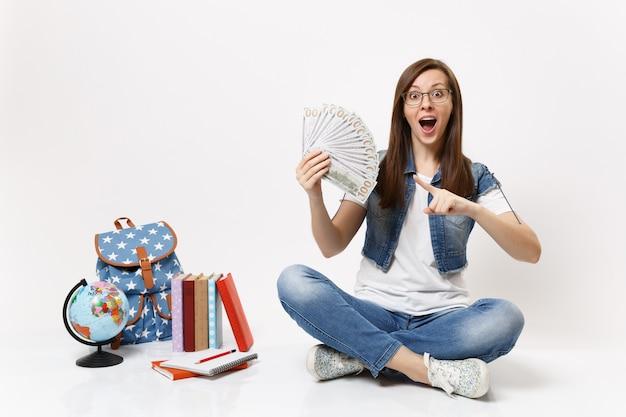 Giovane studentessa sorpresa che punta il dito indice su un sacco di dollari, denaro contante seduto vicino al globo, zaino, libri isolati