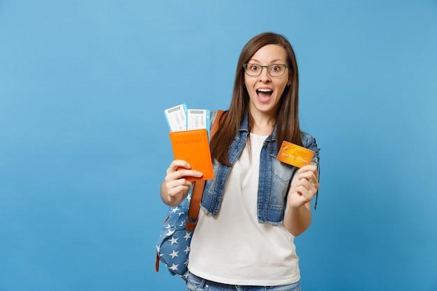 Молодой удивленный студент-женщина с рюкзаком с открытым ртом, держащим кредитную карту билетов на посадочный талон паспорта, изолированную на синем фоне. обучение в вузе за рубежом. авиаперелет.