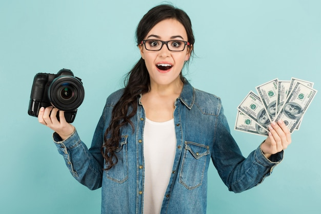 Young surprised woman with camera and cash