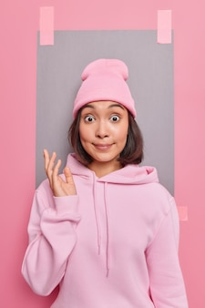 Young surprised young asian woman stares bugged eyes keeps hand raised with indignation wears casual sweatshirt and hat poses against pink backgroud with blank empty space for your advertisement