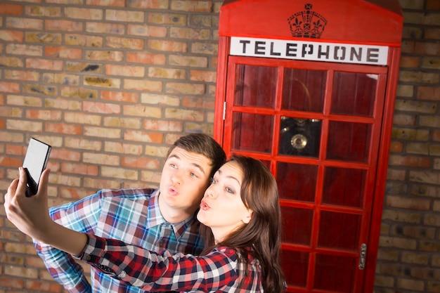 電話ブースの前で自分撮り写真を撮るチェッカーシャツを着た若い甘いカップル。