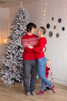 12月に自宅で贈り物と木の近くのクリスマスイブにキスを愛する若い甘いかわいいカップル。