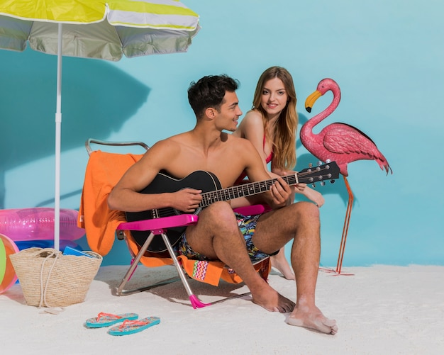Young sweethearts relaxing on beach in studio