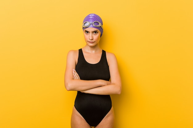 Young swimmer caucasian woman frowning face in displeasure, keeps arms folded.