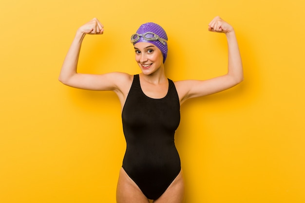Young swimmer caucasian woman showing strength gesture with arms, symbol feminine power