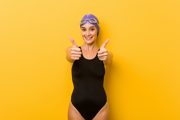 Young swimmer caucasian woman with thumbs ups, cheers about something, support and respect concept.