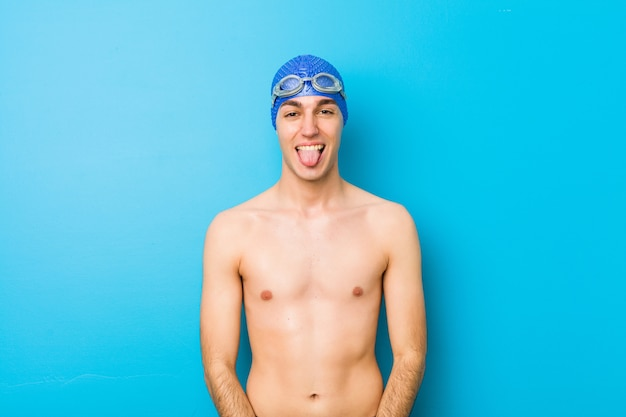 Young swimmer man funny and friendly sticking out tongue.