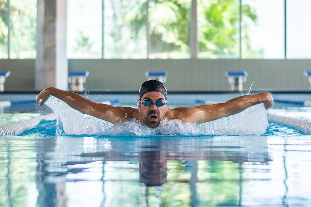 Young swimmer man swimming in an olympic pool