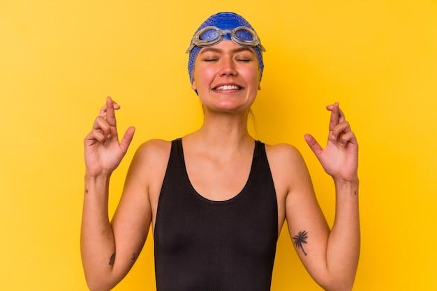 Молодая венесуэльская женщина-пловец изолирована на желтом фоне, скрестив пальцы за удачу