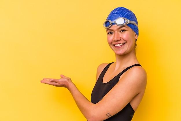 Венесуэльская женщина молодой пловец, изолированные на желтом фоне, держа копию пространства на ладони.