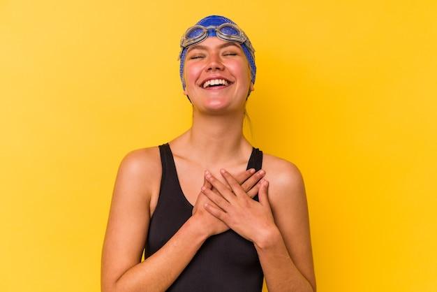 젊은 수영 베네수엘라 여자 마음, 행복의 개념에 유지 손을 웃 고 노란색 배경에 고립.