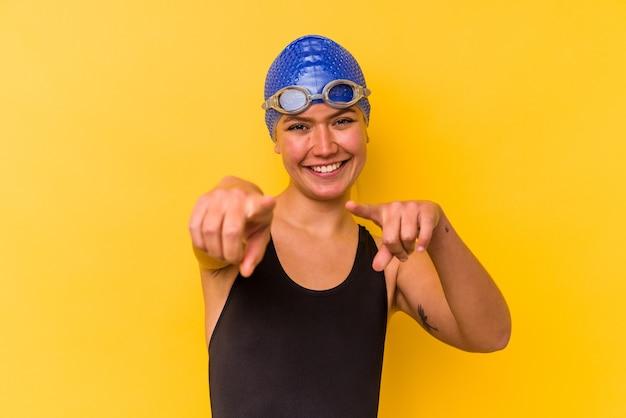 노란색 벽에 고립 된 젊은 수영 베네수엘라 여자 앞을 가리키는 밝은 미소.