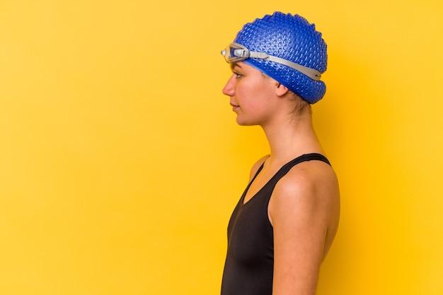 왼쪽, 옆으로 포즈를 응시하는 노란색 벽에 고립 된 젊은 수영 베네수엘라 여자.