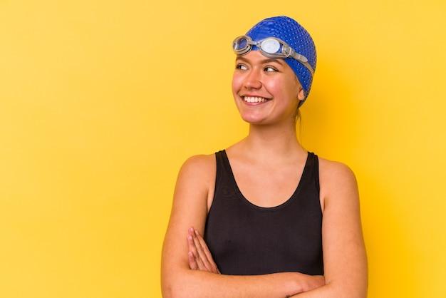 腕を組んで自信を持って笑顔の黄色い壁に隔離された若いスイマーベネズエラの女性。