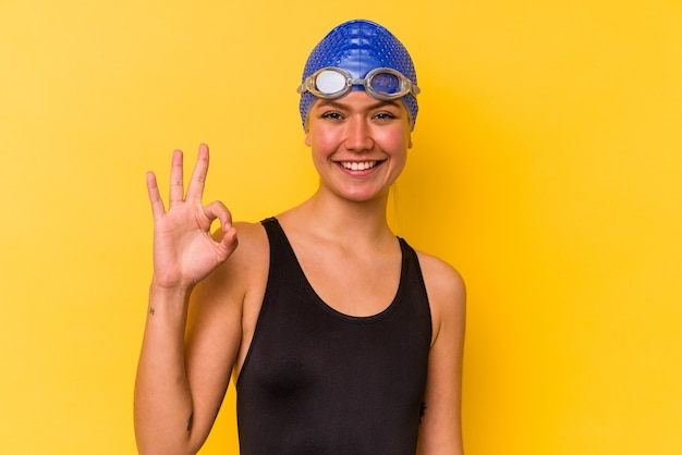 Young swimmer venezuelan woman isolated on yellow background cheerful and confident showing ok gesture.