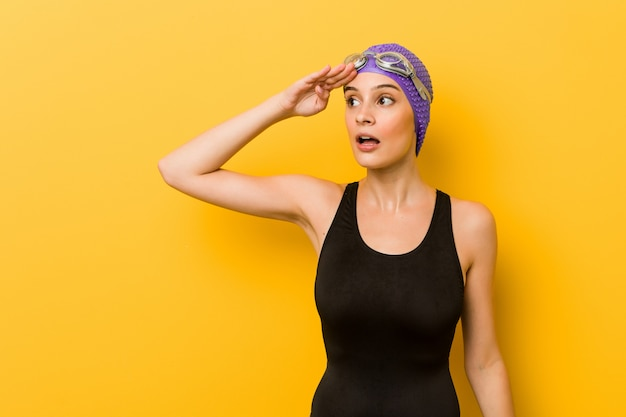 Young swimmer woman looking far away keeping hand on forehead