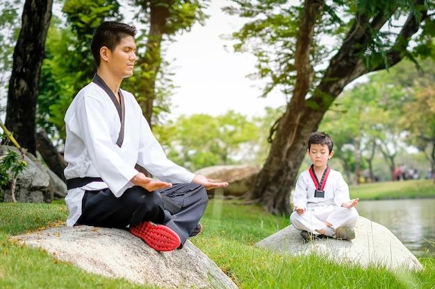 젊은 태권도 남자와 아들 모에 자연 공원에서 돌에 앉아 명상을 하