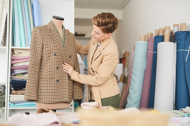 Young tailor hanging jacket on mannequin and examining it before show it to the client in the workshop