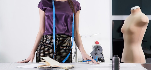 Young tailor at her workshop designing new clothes, atelier studio