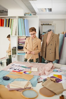 Young tailor standing and looking at the table with fabric and sketches she making new clothes for new collection