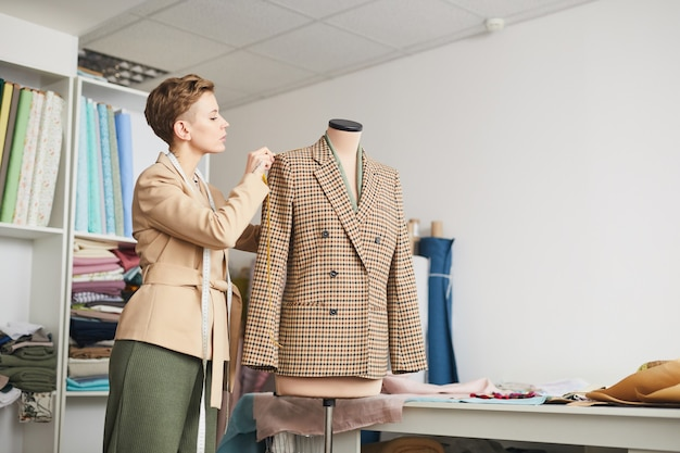 Young tailor taking measurements from jacket on mannequin while working in the workshop