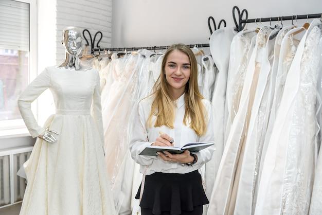 結婚式のサロンでメモ帳と若い仕立て屋