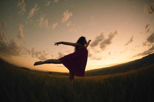 Молодая талантливая танцовщица поднимает ногу в поле полевых цветов во время великолепного заката