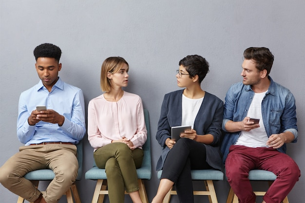 Young talented enterpreneurs have discussion, sit on chairs in queue