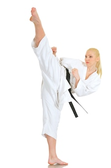 Young talented girl blonde professional karate athlete in a kimono suit with a black belt shows a kick and a good stretch on a white background