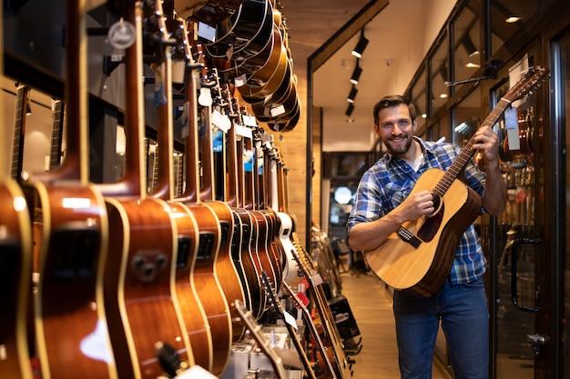 Молодой талантливый музыкант тестирует новый гитарный инструмент в музыкальном магазине.