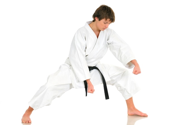 Young talented professional karate guy in a kimono suit with a black belt shows a fighting stance posing