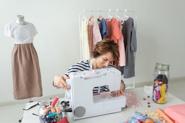 Молодая талантливая женщина-дизайнер одежды шьет свой новый продукт, сидя за своим столом со швейной машиной