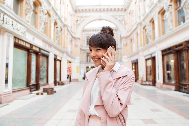 通りに立っている間携帯電話で話している若い