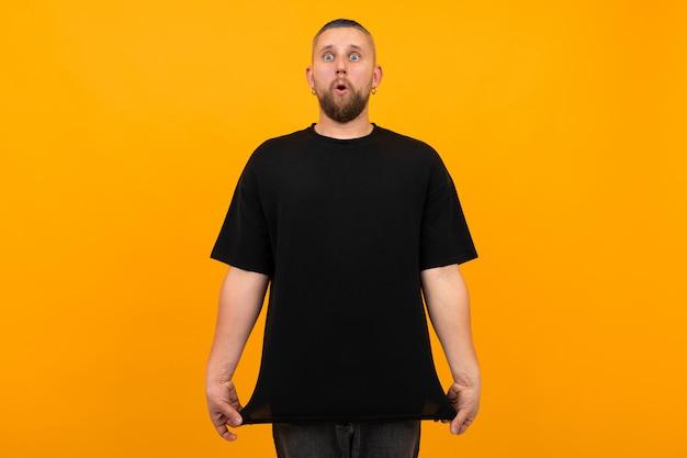 오렌지 배경에 고립 된 검은 티셔츠 미소에 짧은 검은 머리를 가진 젊은 키 큰 남자