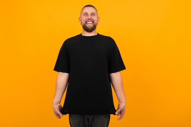 오렌지에 고립 된 검은 티셔츠 미소에 짧은 검은 머리를 가진 젊은 키 큰 남자
