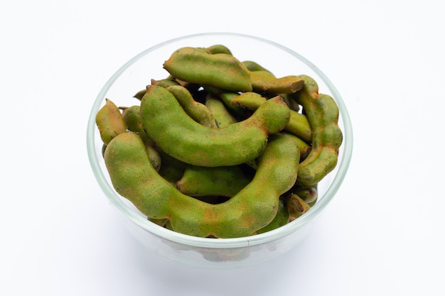 Young tamarind in glass bowl on white background.