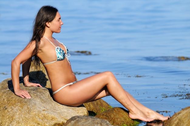 水着の日焼け少女、笑みを浮かべて、海岸の岩の上に背中に横たわっている間ポーズ