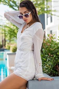 수영장 파티를 즐기는 세련된 여름 옷에 젊은 황갈색 모델. boho 액세서리, 트렌디 한 선글라스.